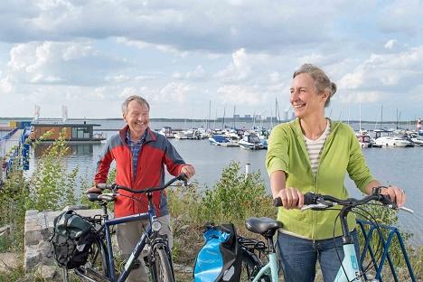 Radfahrer am Großräschener See. Im Hintergrund ist die Seebrücke zu sehen, die aus einem Tagebaugerät gefertigt wurde.